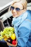 Blonde Frau der Junge recht mit Lebensmittel beim Taschengehen Lizenzfreie Stockfotos