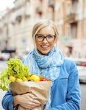 Blonde Frau der Junge recht mit Lebensmittel beim Taschengehen Lizenzfreie Stockbilder