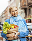 Blonde Frau der Junge recht mit Lebensmittel beim Taschengehen Stockbild