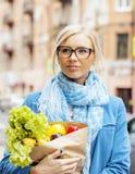 Blonde Frau der Junge recht mit Lebensmittel beim Taschengehen Stockfotografie