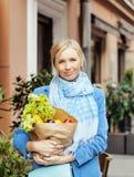 Blonde Frau der Junge recht mit Lebensmittel beim Taschengehen Stockfotos