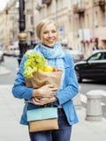 Blonde Frau der Junge recht mit Lebensmittel in der Tasche gehend auf Straße Lizenzfreie Stockfotografie