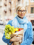 Blonde Frau der Junge recht mit Lebensmittel in der Tasche gehend auf Straße Stockfoto