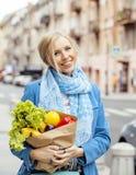 Blonde Frau der Junge recht mit Lebensmittel in der Tasche gehend auf Straße Stockfotografie