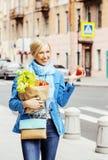 Blonde Frau der Junge recht mit Lebensmittel in der Tasche gehend auf Straße Lizenzfreie Stockfotos