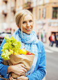 Blonde Frau der Junge recht mit Lebensmittel in der Tasche gehend auf Straße Lizenzfreies Stockbild