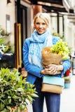 Blonde Frau der Junge recht mit Lebensmittel in der Tasche gehend auf Straße Lizenzfreies Stockfoto