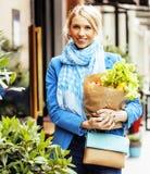 Blonde Frau der Junge recht mit Lebensmittel in der Tasche gehend auf Straße Stockbild