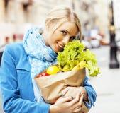 Blonde Frau der Junge recht mit Lebensmittel in der Tasche gehend auf Straße Lizenzfreie Stockbilder