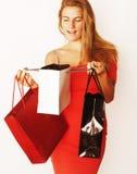 Blonde Frau der Junge recht mit Taschen auf Weihnachtsverkauf in den roten dres Stockfotos
