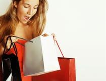 Blonde Frau der Junge recht mit Taschen auf Weihnachtsverkauf im roten Kleid lokalisierte Weiß Lizenzfreie Stockfotografie