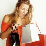 Blonde Frau der Junge recht mit Taschen auf Weihnachtsverkauf im roten Kleiderweiß-Hintergrundlächeln Stockbilder