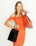 Blonde Frau der Junge recht mit Taschen auf Weihnachtsverkauf im roten Kleiderweiß-Hintergrundlächeln Stockbild