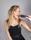 Blonde Frau der Junge recht singen im Mikrofon Lizenzfreie Stockfotos