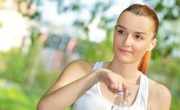Blonde Frau der Junge vitaly, die Trinkwasser hält Lizenzfreie Stockfotografie