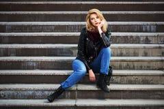 Blonde Frau der jungen Mode in der Lederjacke, die auf den Schritten sitzt Lizenzfreie Stockfotografie
