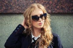 Blonde Frau der jungen Mode in der Sonnenbrille an der Wand Stockbild