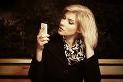 Blonde Frau der jungen Mode, die Handy betrachtet Stockfoto