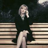 Blonde Frau der jungen Mode, die am Handy sitzt auf Bank spricht Lizenzfreie Stockbilder