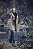 Blonde Frau der jungen Mode, die in Herbstwald geht Lizenzfreies Stockbild