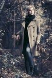 Blonde Frau der jungen Mode, die in Herbstwald geht Stockfoto
