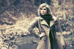 Blonde Frau der jungen Mode, die in Herbstwald geht Stockbilder