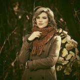 Blonde Frau der jungen Mode, die in Herbstwald geht Lizenzfreie Stockbilder