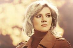 Blonde Frau der jungen Mode, die in Herbstwald geht Stockfotografie