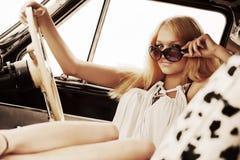Blonde Frau der jungen Mode, die im Retro- Auto sich entspannt Lizenzfreies Stockfoto