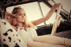 Blonde Frau der jungen Mode, die im Weinleseauto sich entspannt Stockbilder
