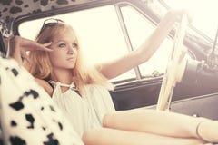 Blonde Frau der jungen Mode, die im Weinleseauto sich entspannt Lizenzfreies Stockfoto