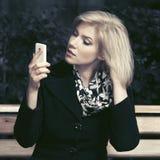 Blonde Frau der jungen Mode, die intelligentes Telefon in der Stadtstraße verwendet Stockbilder