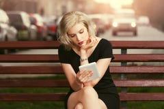 Blonde Frau der jungen Mode, die Tablet-Computer auf der Bank verwendet Stockfoto