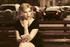 Blonde Frau der jungen Mode, die Tablet-Computer in der Stadtstraße verwendet Lizenzfreie Stockfotos