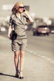 Blonde Frau der jungen Mode, die um Handy auf Stadtstraße ersucht Stockbilder