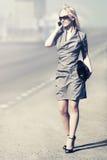 Blonde Frau der jungen Mode, die um Handy in der Stadtstraße ersucht Lizenzfreie Stockfotografie