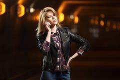 Blonde Frau der jungen Mode, die um Handy ersucht Lizenzfreie Stockbilder