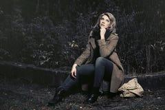 Blonde Frau der jungen Mode im klassischen beige Mantel im Freien Stockbilder