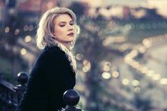Blonde Frau der jungen Mode im schwarzen Mantel auf Stadtstraße Stockbilder