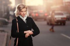 Blonde Frau der jungen Mode im schwarzen Mantel gehend in Stadtstraße Lizenzfreies Stockbild