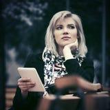 Blonde Frau der jungen Mode mit dem Tablet-Computer, der auf Bank sitzt Lizenzfreie Stockfotos