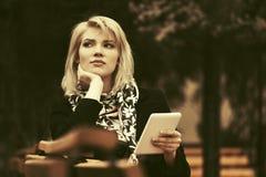 Blonde Frau der jungen Mode mit dem Tablet-Computer, der auf Bank sitzt Lizenzfreie Stockfotografie