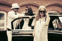 Blonde Frau der jungen Mode nahe bei Retro- Auto Lizenzfreies Stockbild