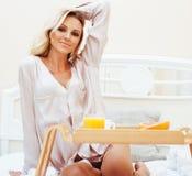 Blonde Frau der jungen Schönheit, die in frühem sonnigem MOR des Betts frühstückt Stockbild