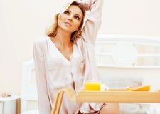 Blonde Frau der jungen Schönheit, die in frühem sonnigem MOR des Betts frühstückt Lizenzfreie Stockbilder