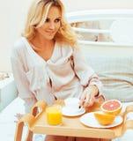 Blonde Frau der jungen Schönheit, die in frühem sonnigem MOR des Betts frühstückt Lizenzfreie Stockfotografie
