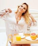 Blonde Frau der jungen Schönheit, die in frühem sonnigem MOR des Betts frühstückt Stockbilder
