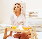 Blonde Frau der jungen Schönheit, die in frühem sonnigem MOR des Betts frühstückt Lizenzfreies Stockbild