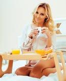 Blonde Frau der jungen Schönheit, die in frühem sonnigem MOR des Betts frühstückt Stockfotos