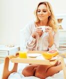 Blonde Frau der jungen Schönheit, die in frühem sonnigem MOR des Betts frühstückt Stockfotografie